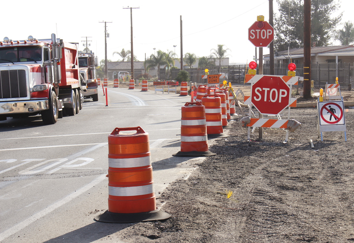 Orange barrels and stop signs in a work zone