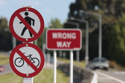 Signs on the off-ramp of a motorway. No cycles, no pedestrians, wrong way.